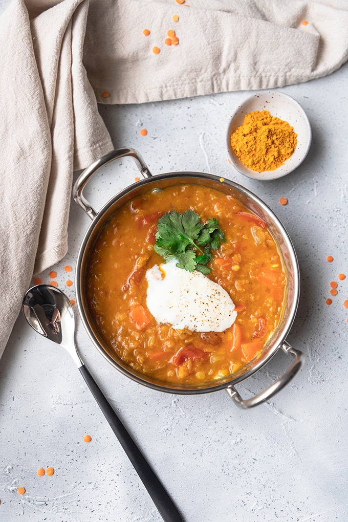 lentil dal in metal dish with spoon and turmeric