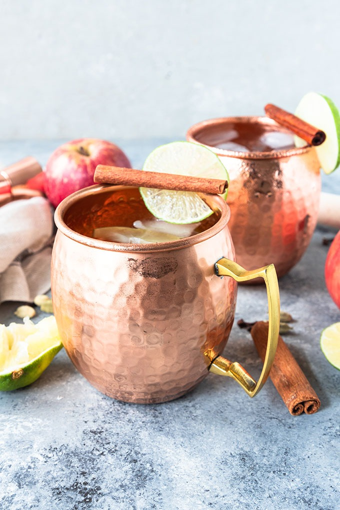 apple cider moscow mules in copper mugs on grey board