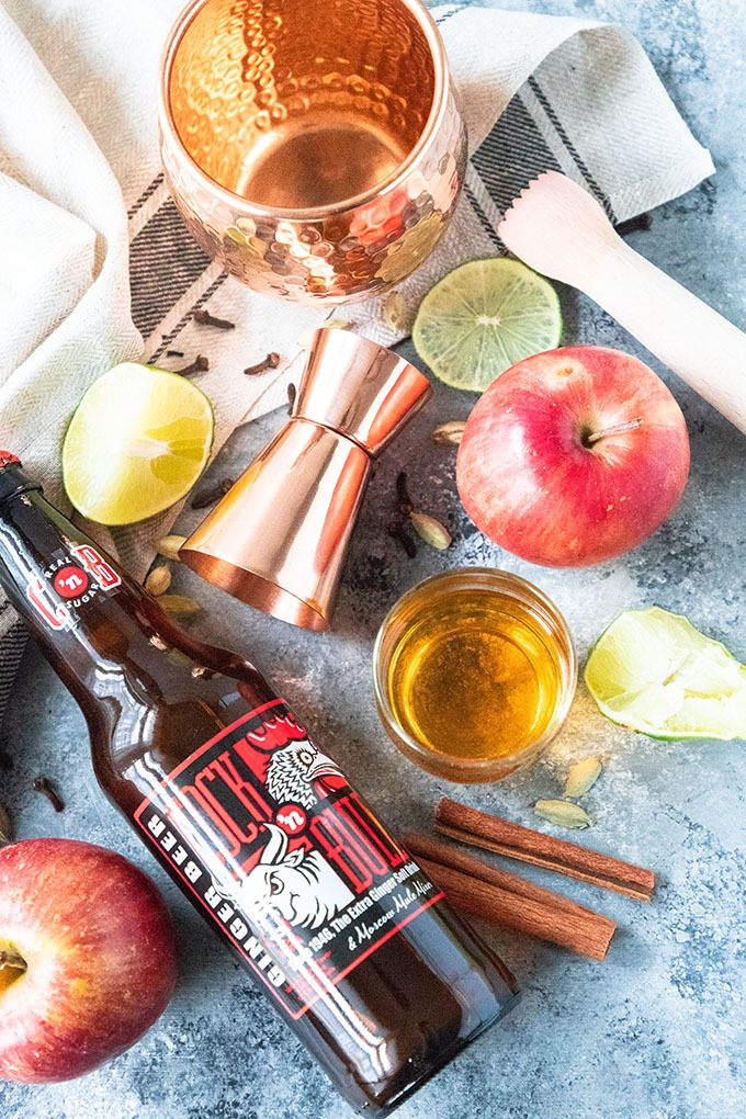 apple cider moscow mule ingredients on board - ginger beer, apples, cinnamon sticks, lime and simple syrup