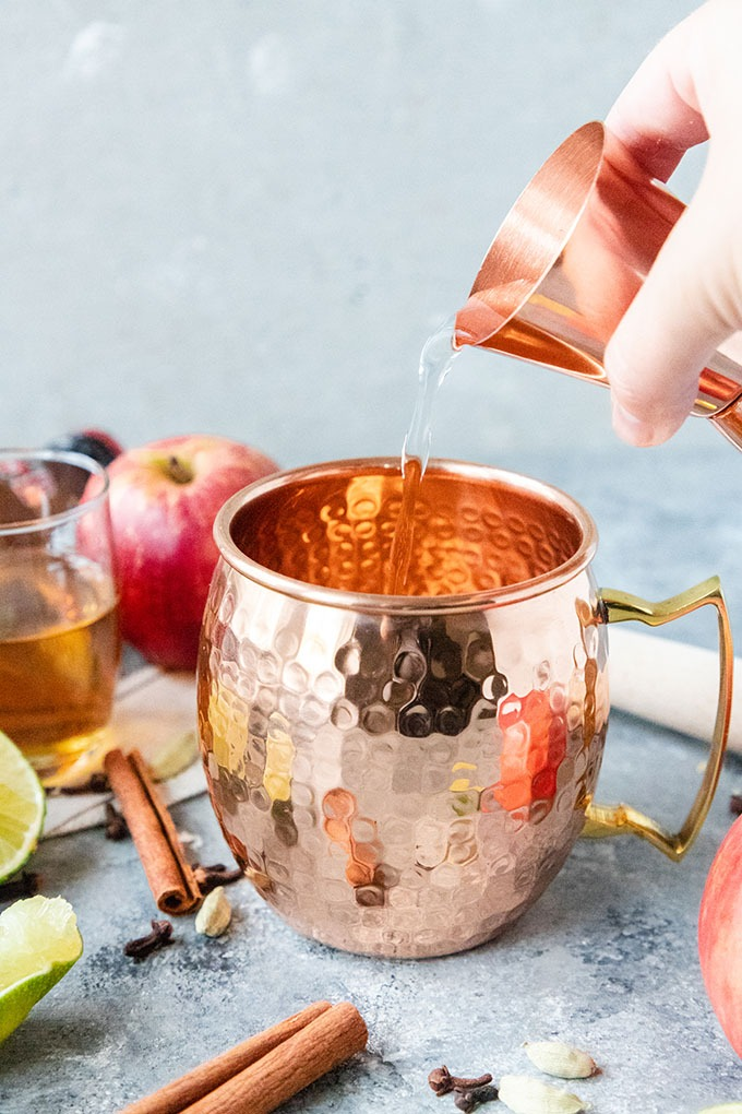 vodka being poured into a copper mug