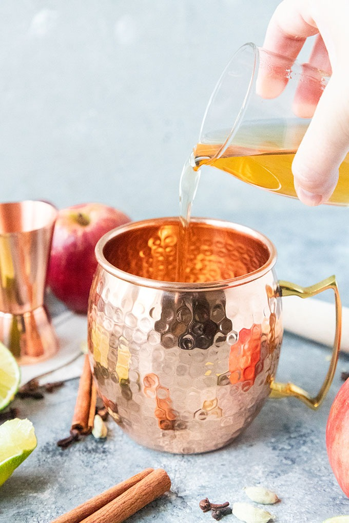 spiced simple syrup being poured into copper mug