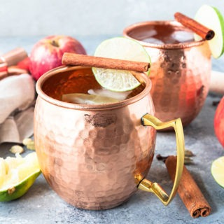 two copper mugs of apple cider moscow mule