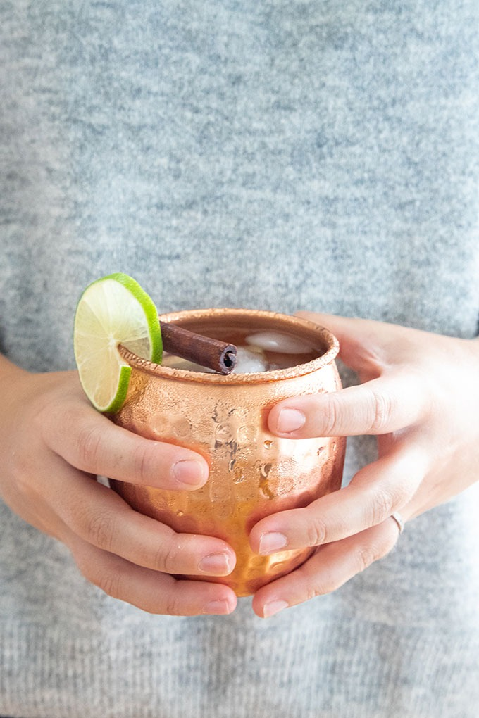 hand holding copper mug of apple cider moscow mule in front of grey sweater