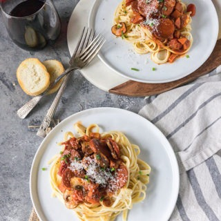 two plates of tomato chorizo pasta with red wine and antique forks