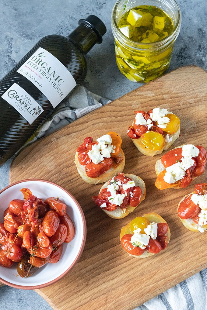 tomato crostini on wooden board with bowl of roasted tomatoes, olive oil and feta jar