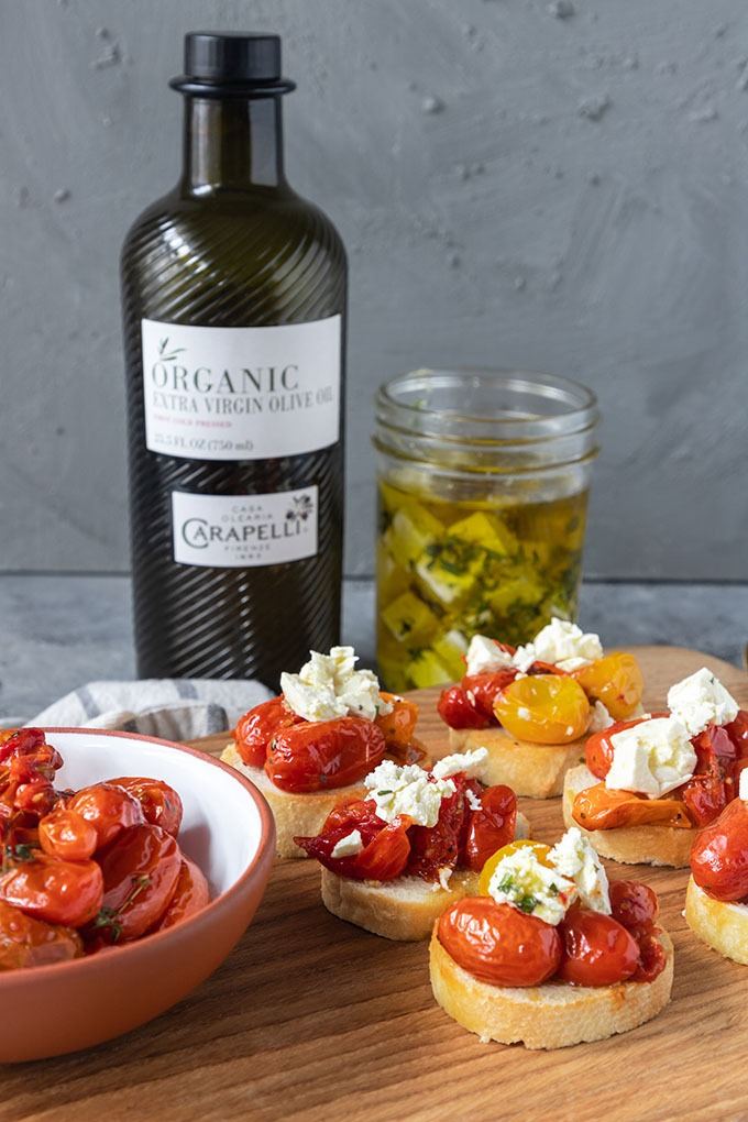 tomato crostinin on wooden board with tomatoes, olive oil and feta