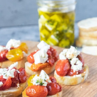 tomato crostini on wooden board in front of marinated feta