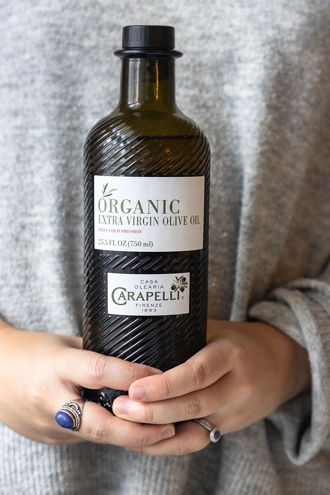 person in grey sweater holding bottle of carapelli olive oil
