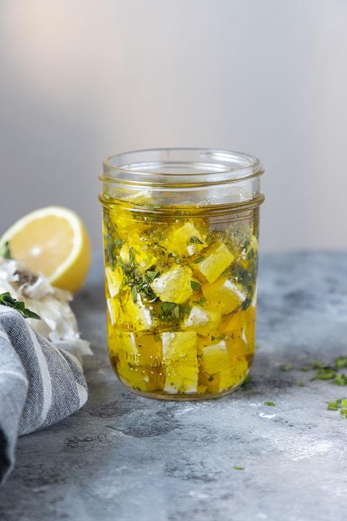 marinated feta in jar on grey board