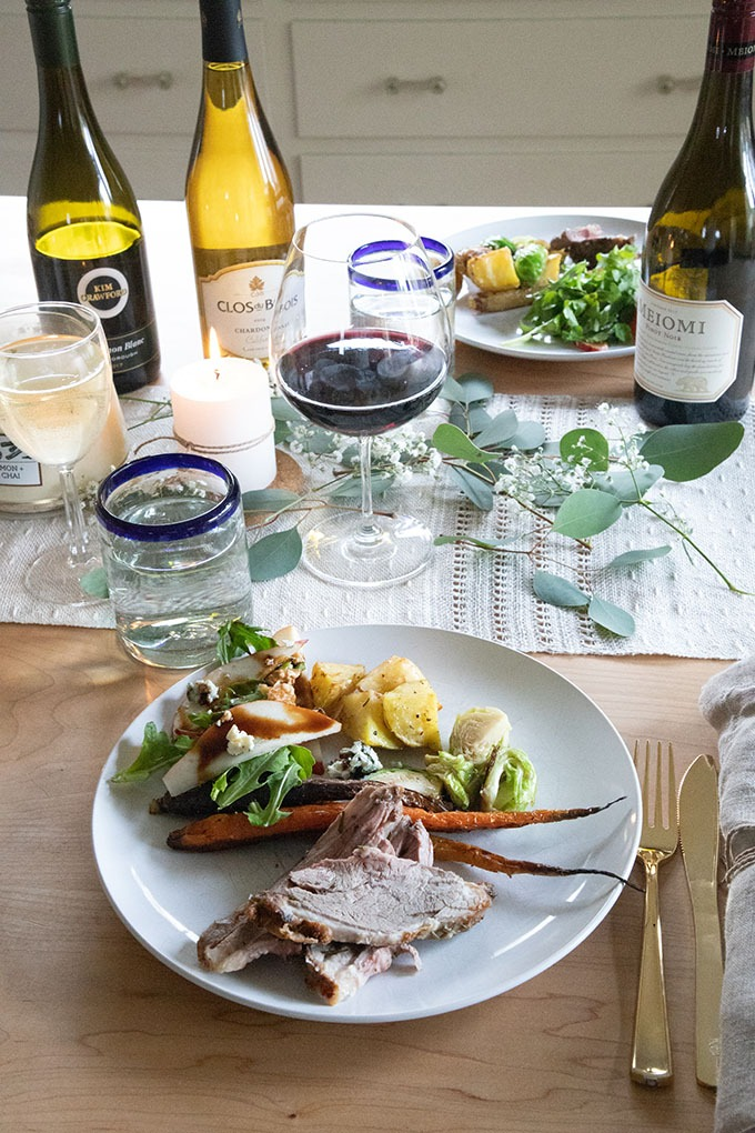 lamb and sides on plate set onto table with wines