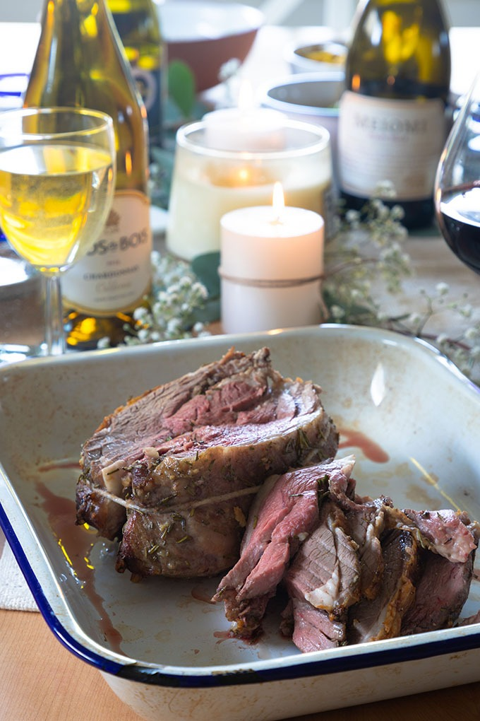 boneless lamb roast on table with Wine and sides in background