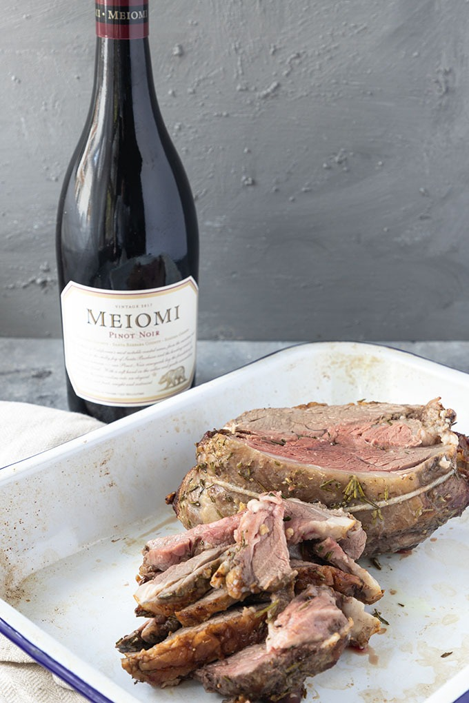 cooked boneless lamb roast with Pinot Noir bottle