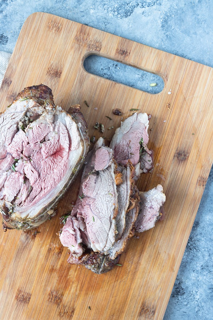 cooked and sliced boneless lamb roast on wooden board