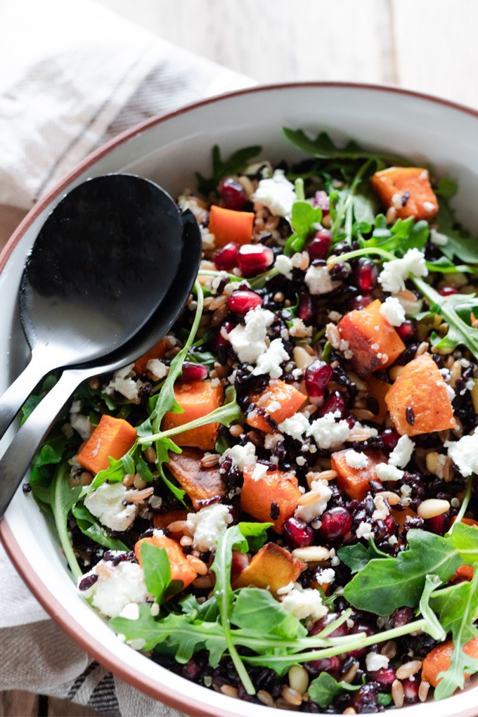 grain salad with black servers in white and brown bowl