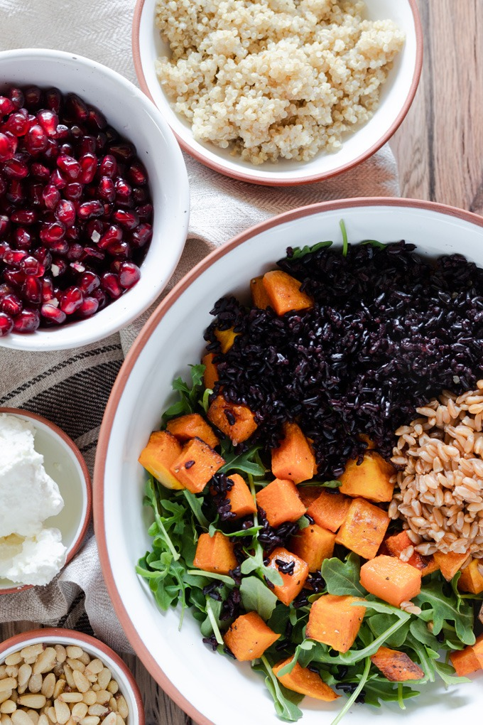 grains, pumpkin and arugula in bowl, with quinoa and pomegranate around side of bowl