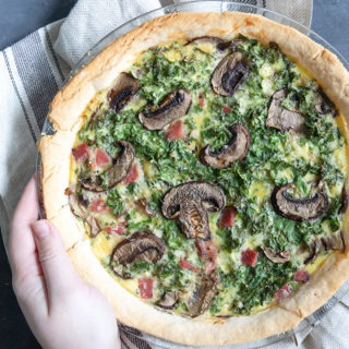 hand holding quiche in glass dish
