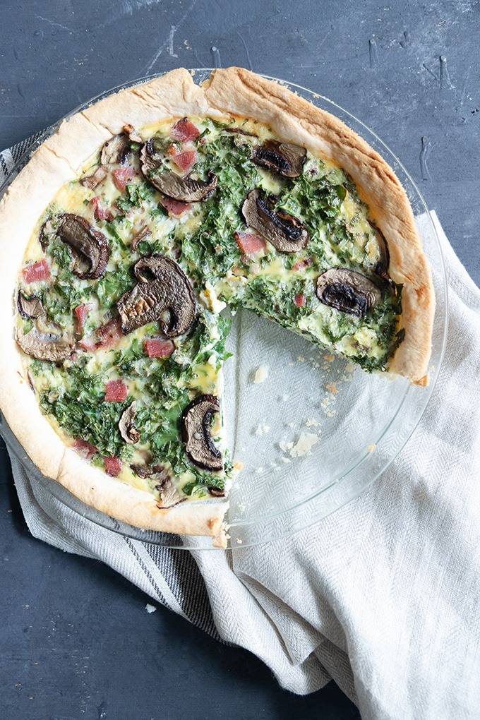 piece of quiche missing from whole quiche in glass pie dish