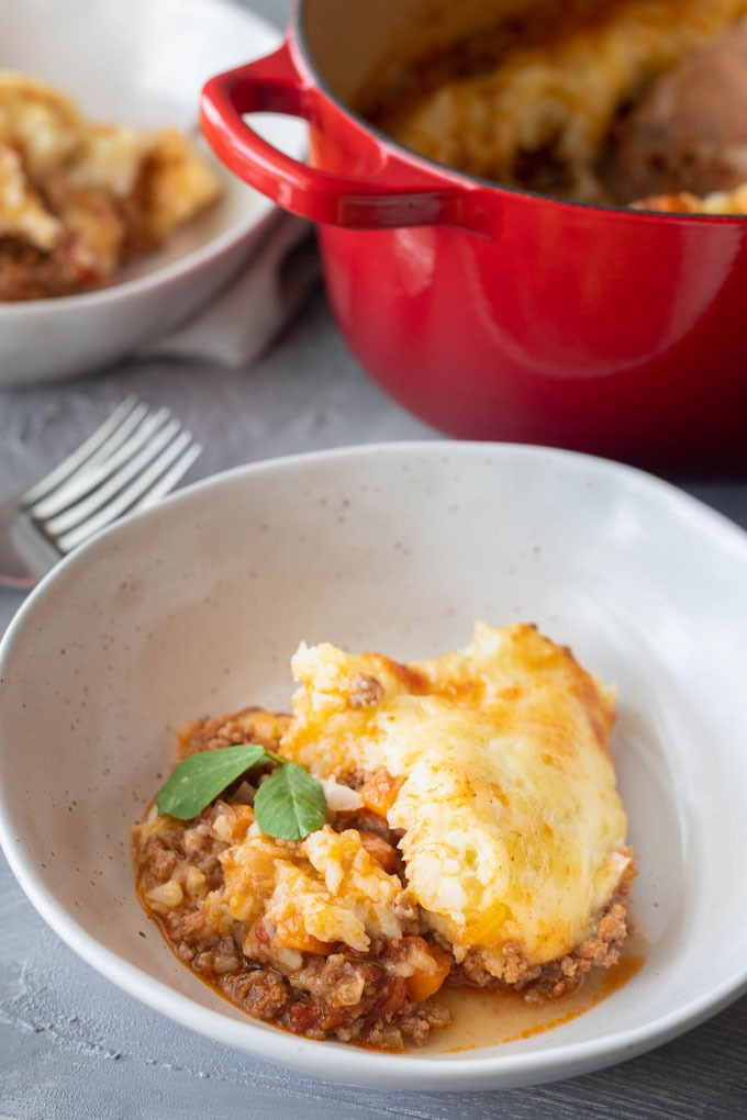 lamb shepherd's pie in white bowl in front of dutch oven