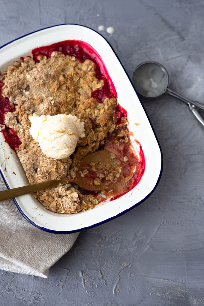 rhubarb crumble in enamel dish with ice cream and scoop