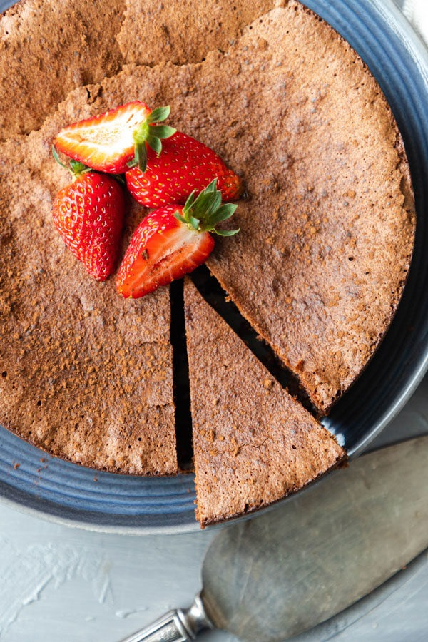 flourless chocolate torte on blue plate with one piece cut
