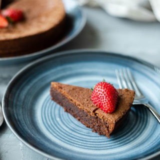 slice of flourless chocolate torte on blue plate