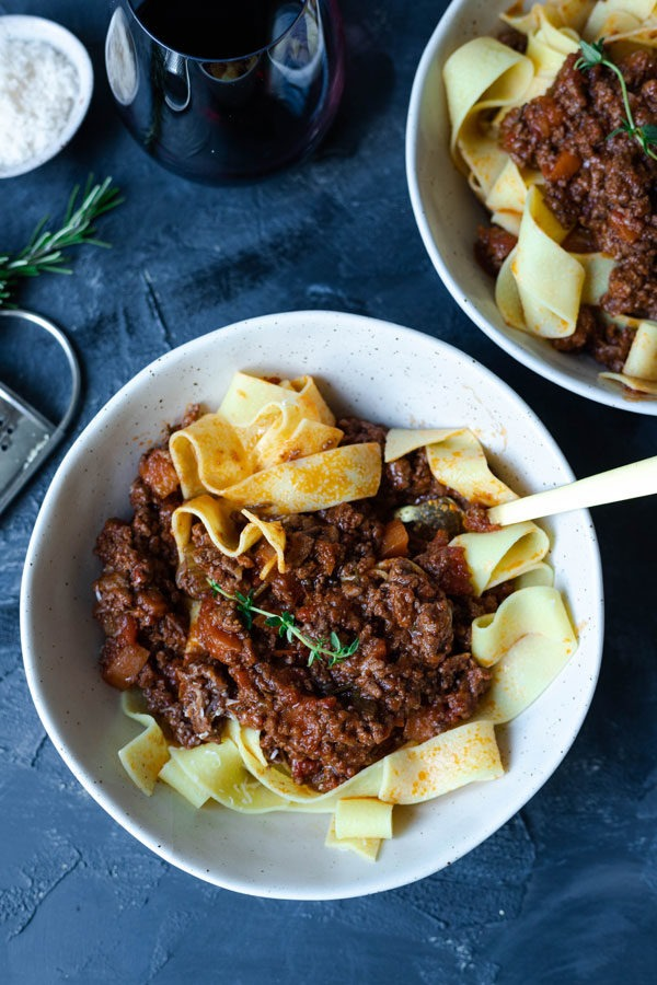 lamb ragu in bowls with fork