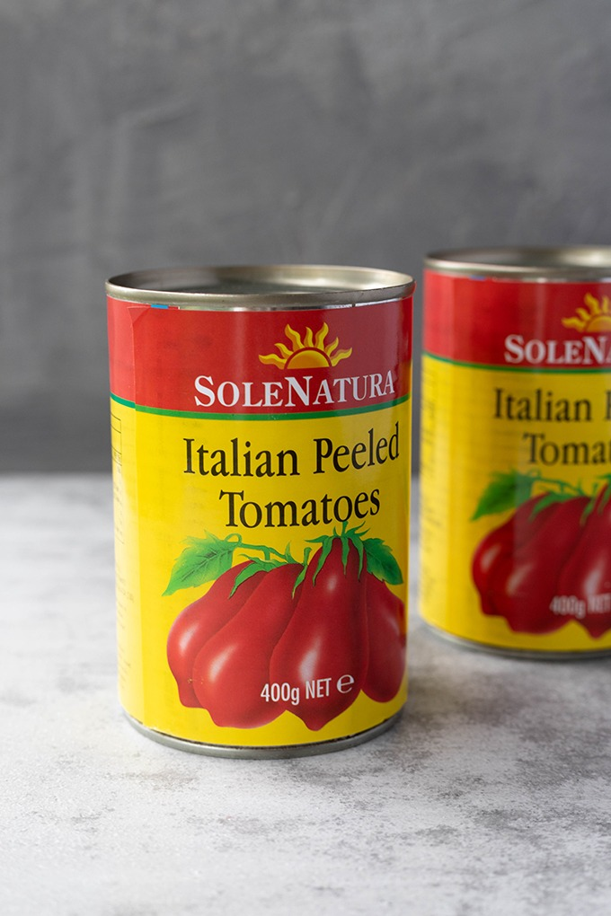 two tins of tomatoes on grey board