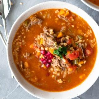 lamb shank soup in a white bowl