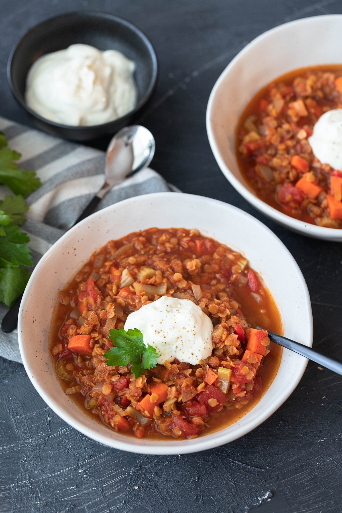 two bowls of spicy lentil soup on board with yogurt pot and spoons