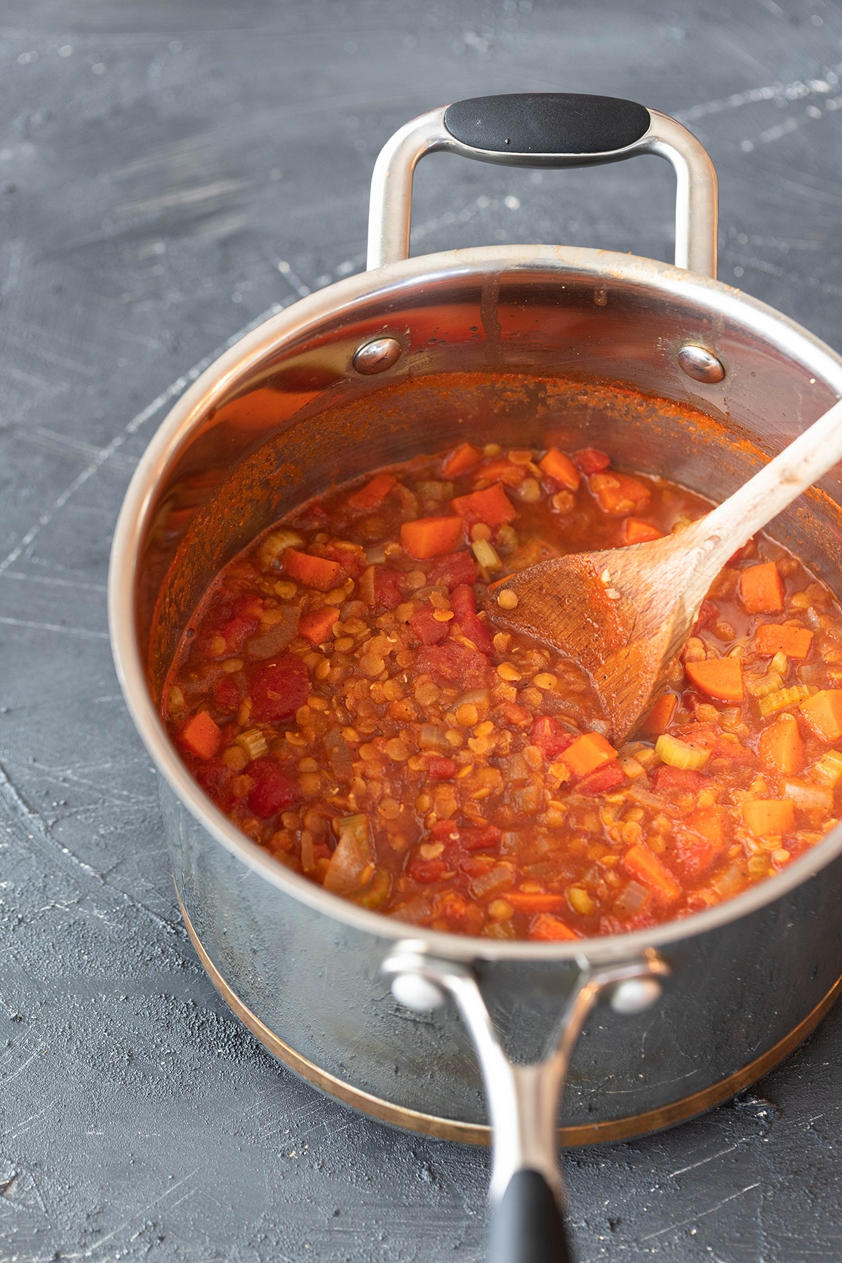 cooked spicy lentil soup in saucepan with wooden spoon