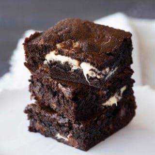 chocolate chip brownies stacked on a small white plate