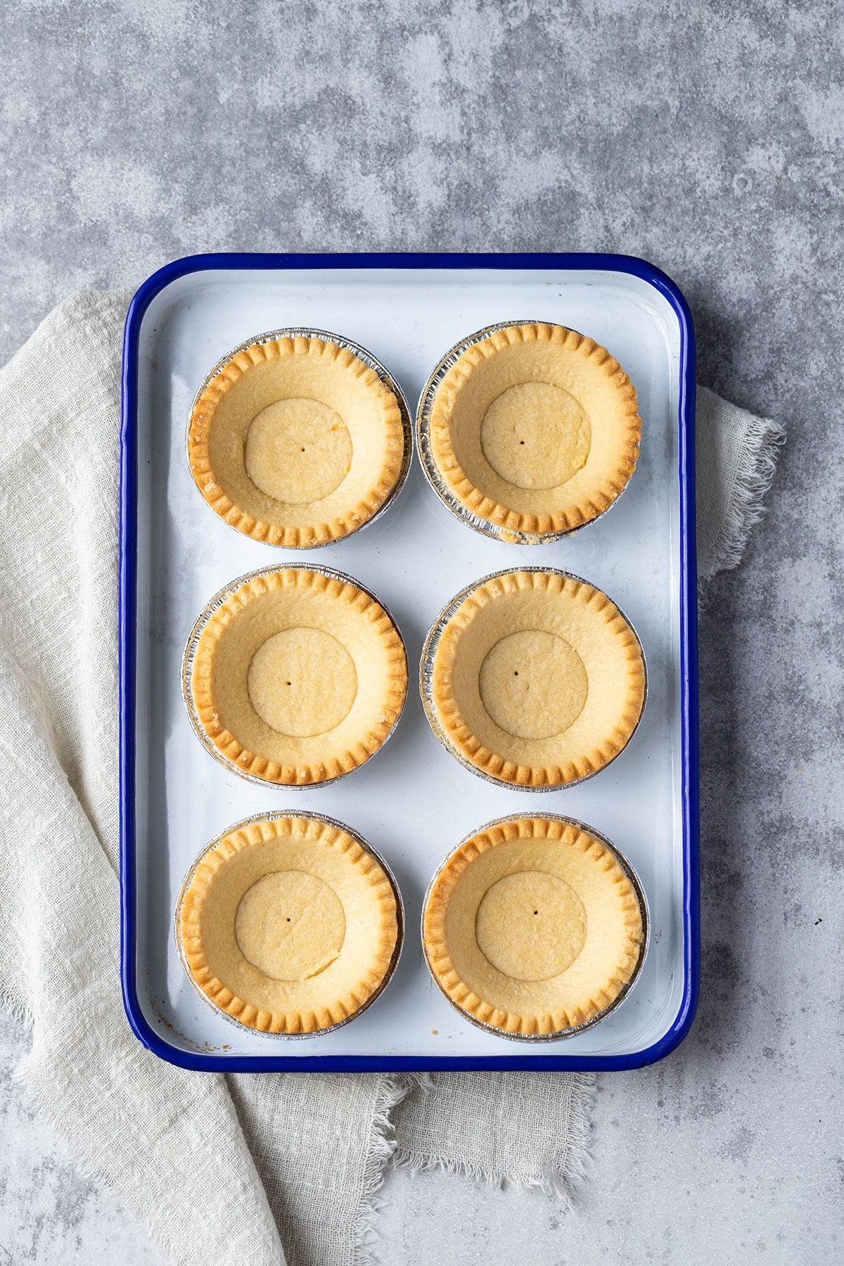 six pastry tart shells on an enamel tray