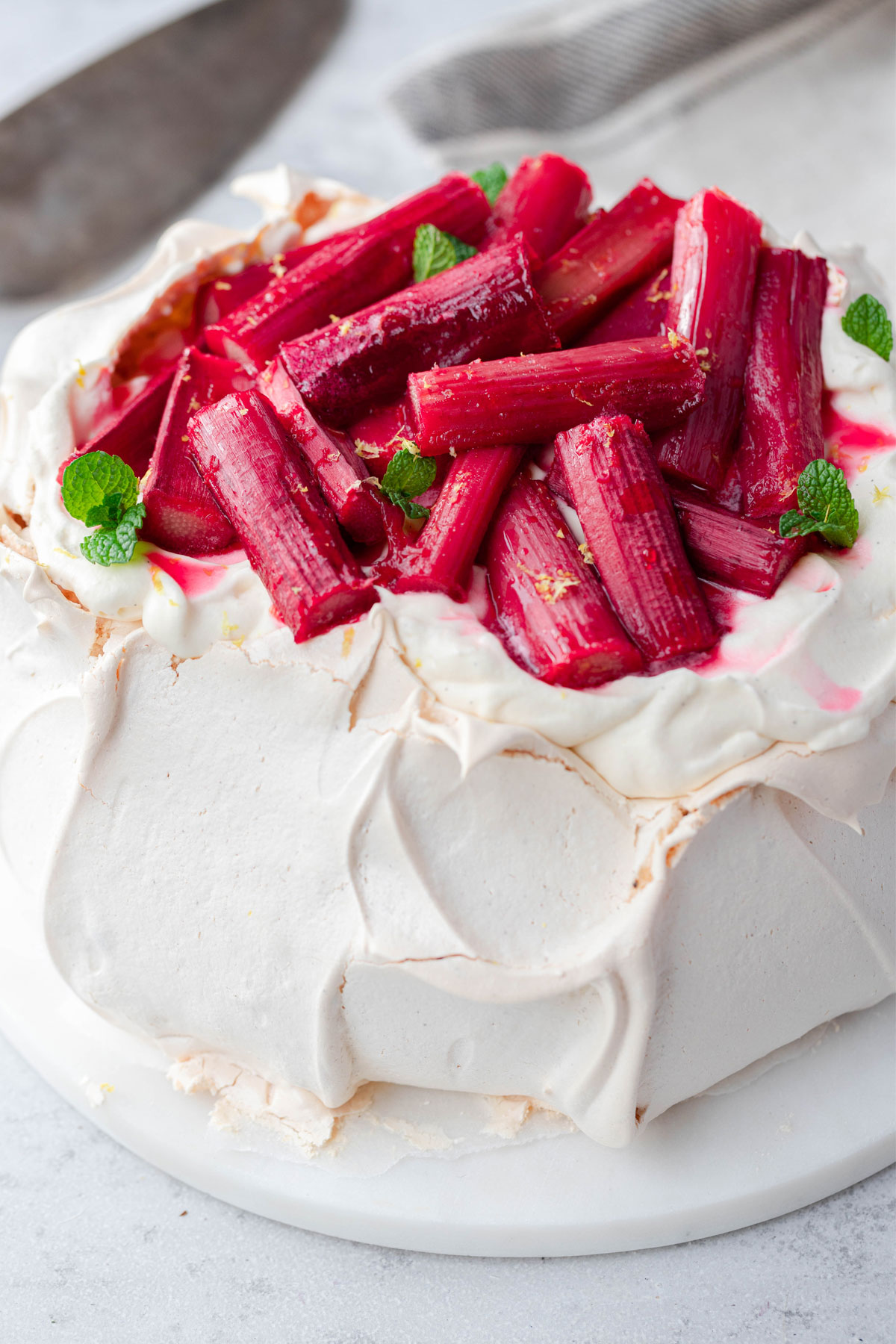 Close up of Christmas pavlova on marble board featuring baked rhubarb