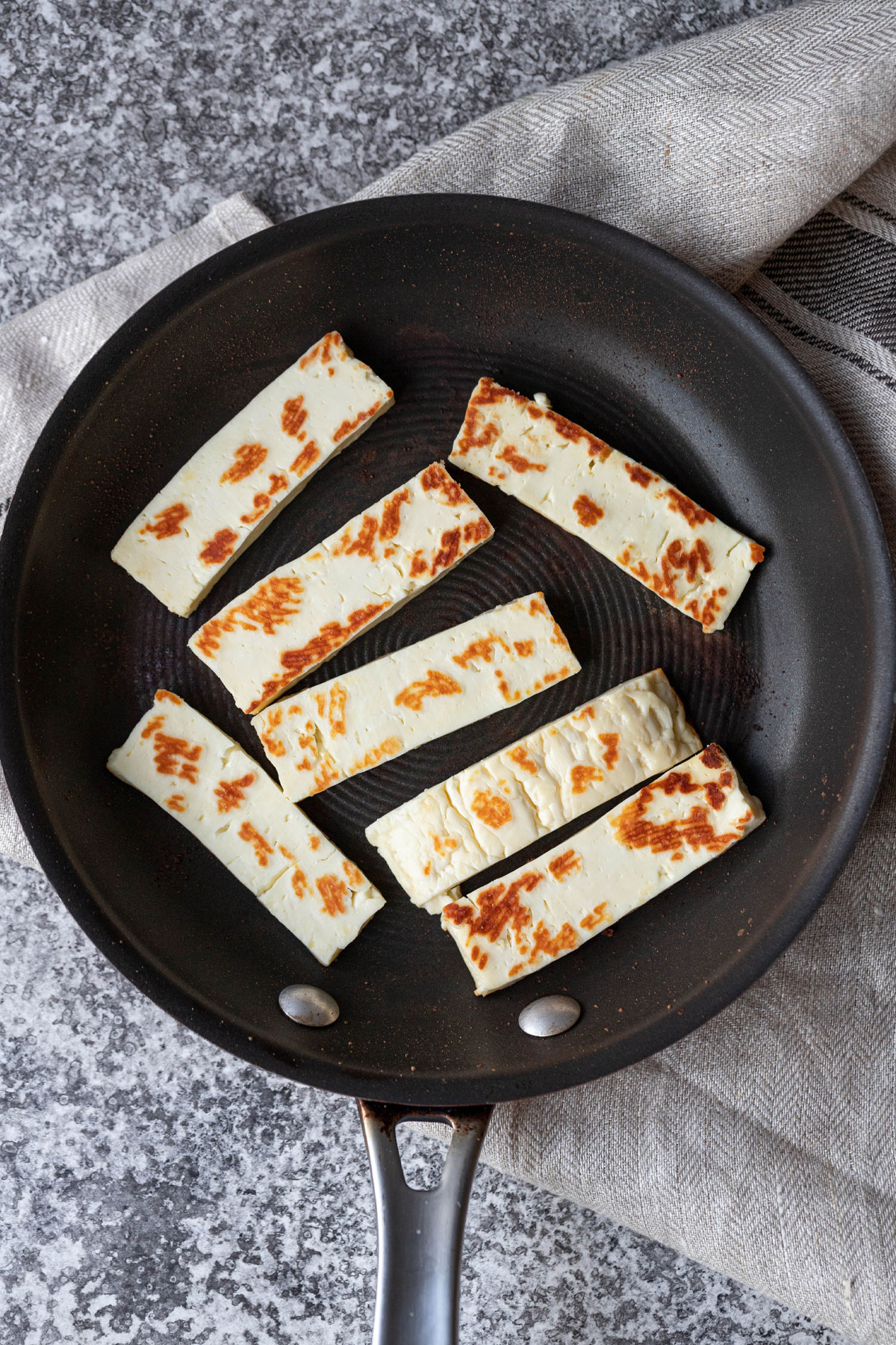 cooked halloumi pieces in a small fry pan
