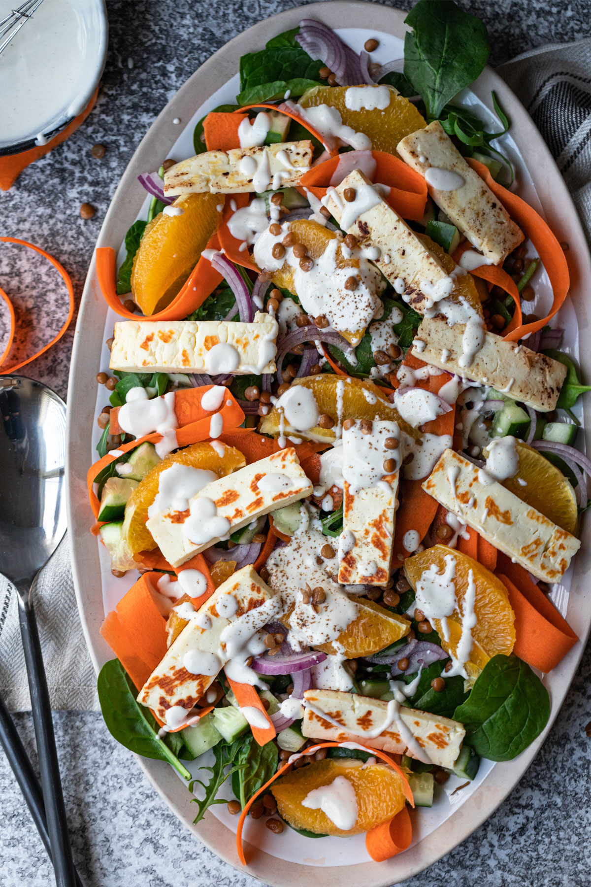 overhead image of lentil halloumi salad on a tan and white platter