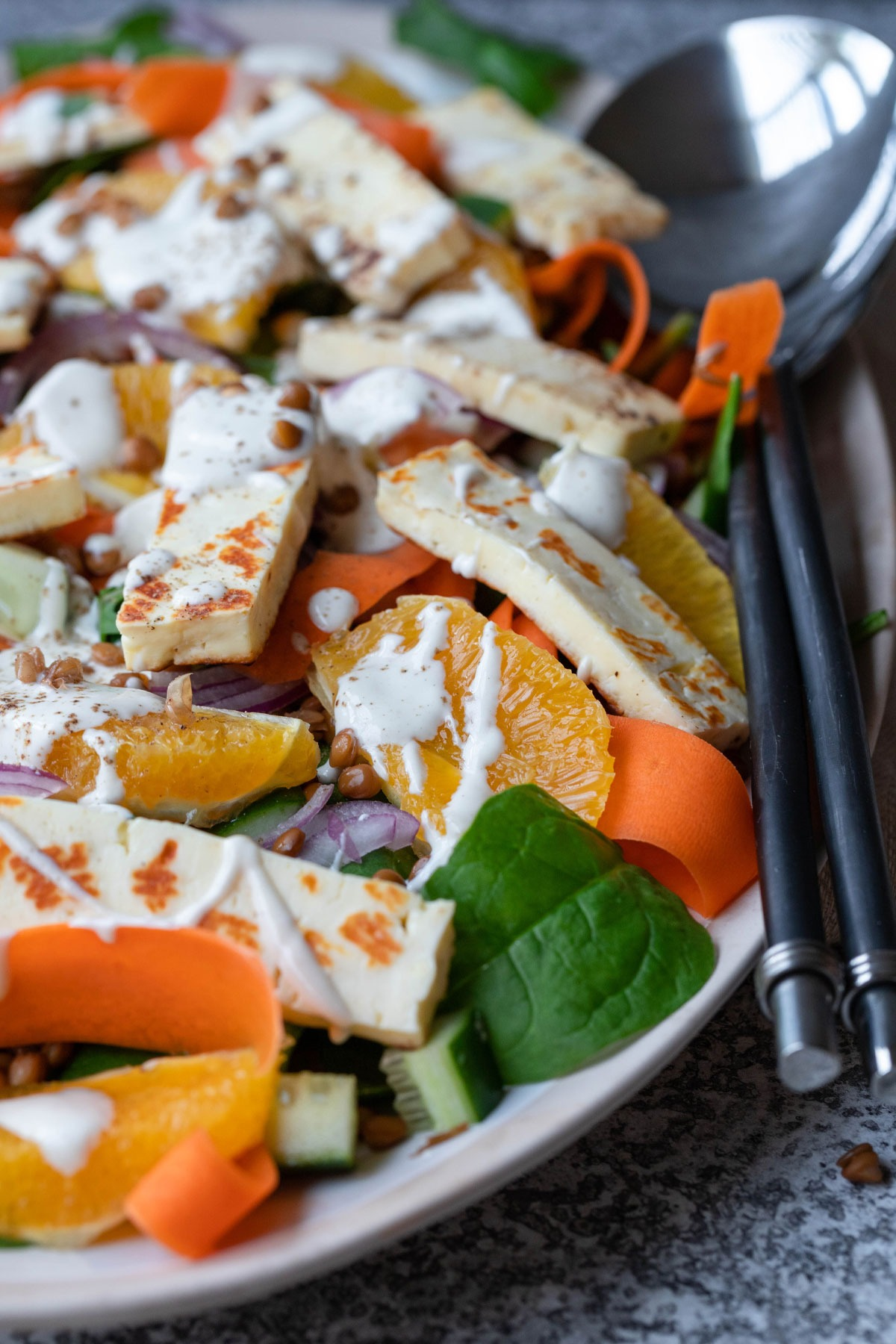 close up lentil halloumi salad on tan and white platter