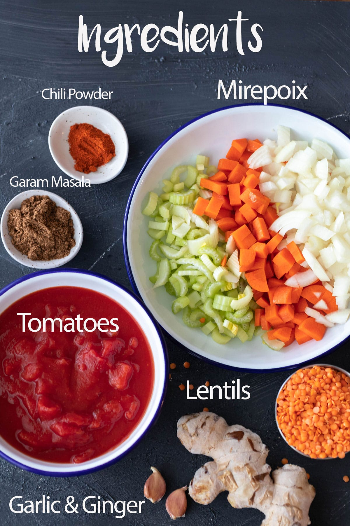spicy lentil soup ingredients chilies powder, garam masala, mirepoix, tomatoes, garlic and ginger and lentils. ingredients laid on a board