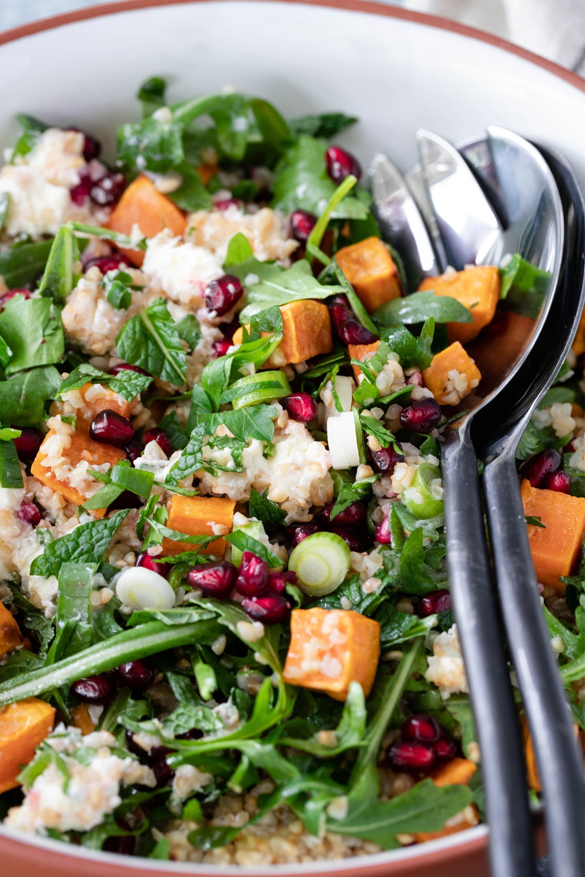 close up roast sweet potato salad in tan and white bowl