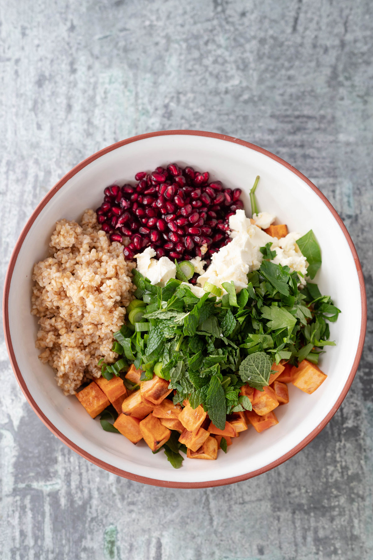 roast sweet potato salad ingredients in a tan and white bowl