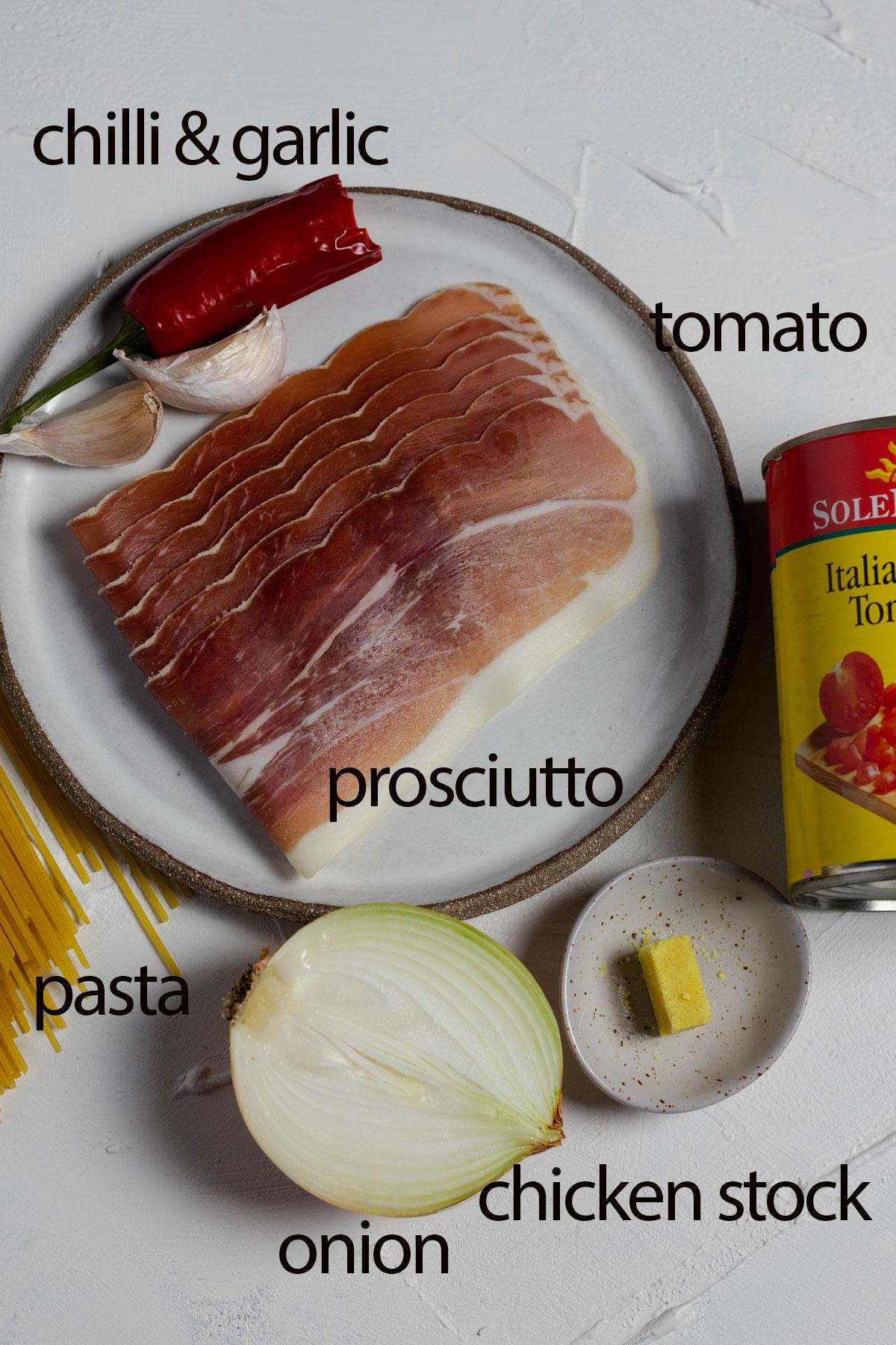 amatriciana ingredients: spaghetti, chilli and garlic, prosciutto, onion, chicken stock and tomato laid on a white board.