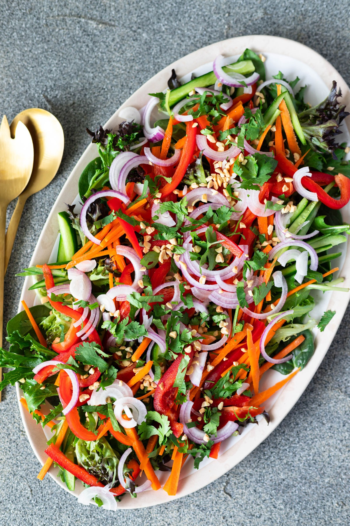 thai salad on large platter with gold serving spoons